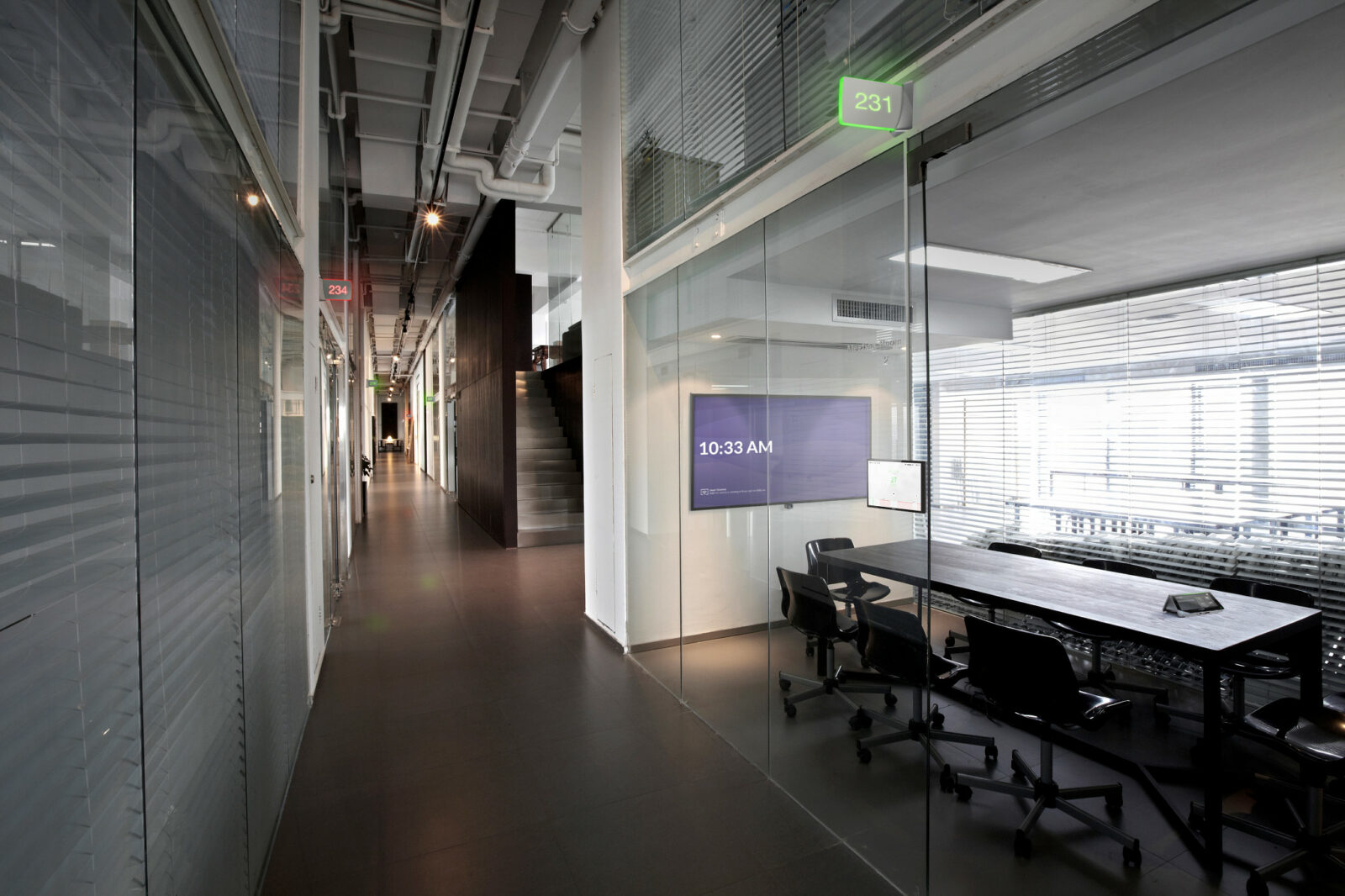 A sleek office interior with digital room scheduling system
