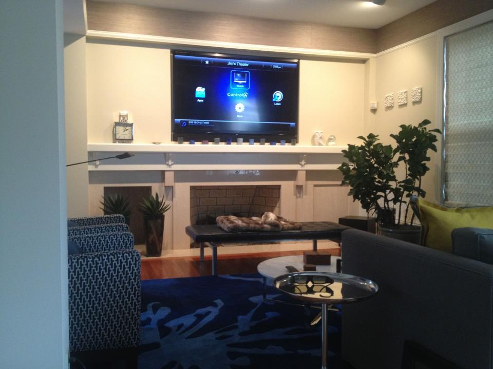 Home theater system installed above a fireplace